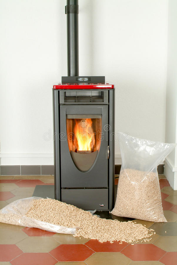 Modern domestic pellet stove with a burning flame. And bags full of particle pellets stock image