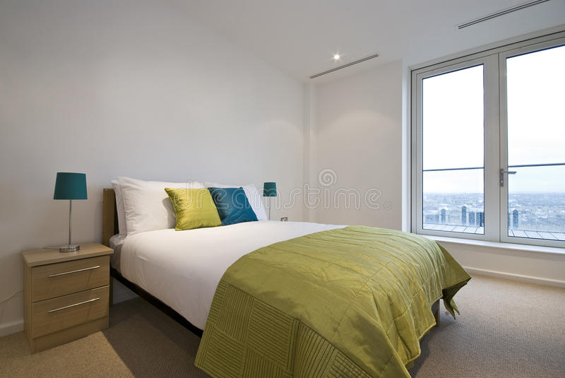 Modern double bedroom with king size bed stock photography