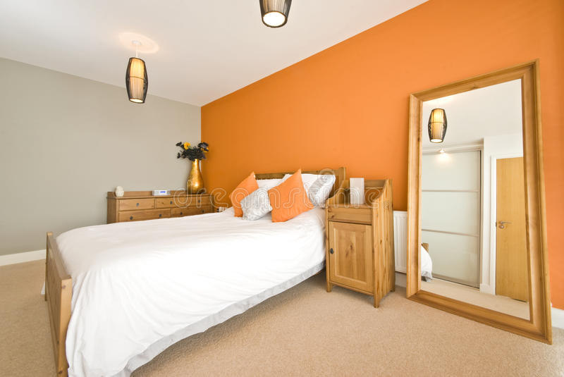 Modern double bedroom with solid wooden furniture. Large mirror, chest of drawers and orange wall royalty free stock image