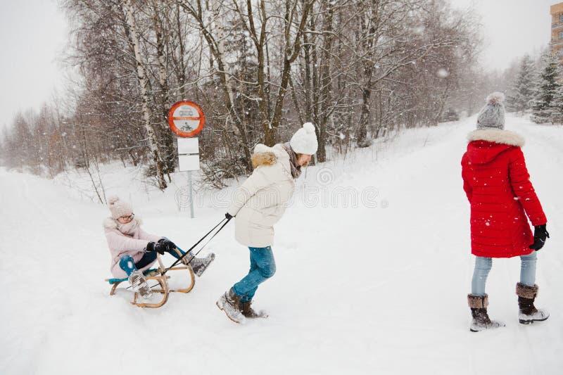 Modern drar hennes dotter på pulkan - att snöa dag arkivbild