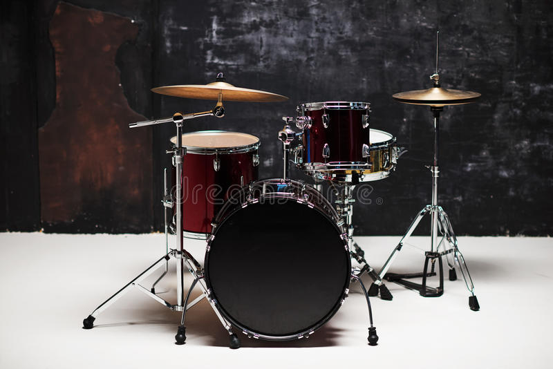 Modern drum set on black background in room. Gold and red color stock image