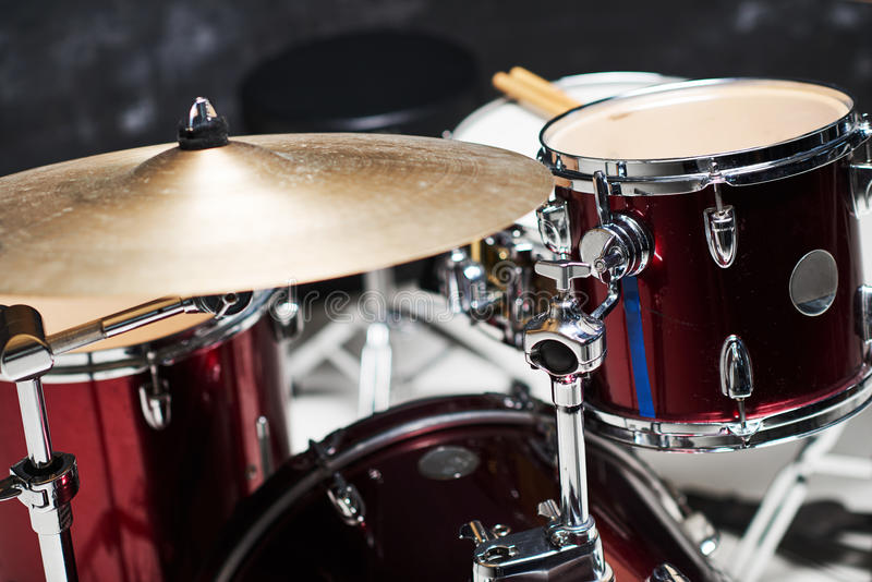 Modern drum set on black background in room. Gold and red color royalty free stock photos