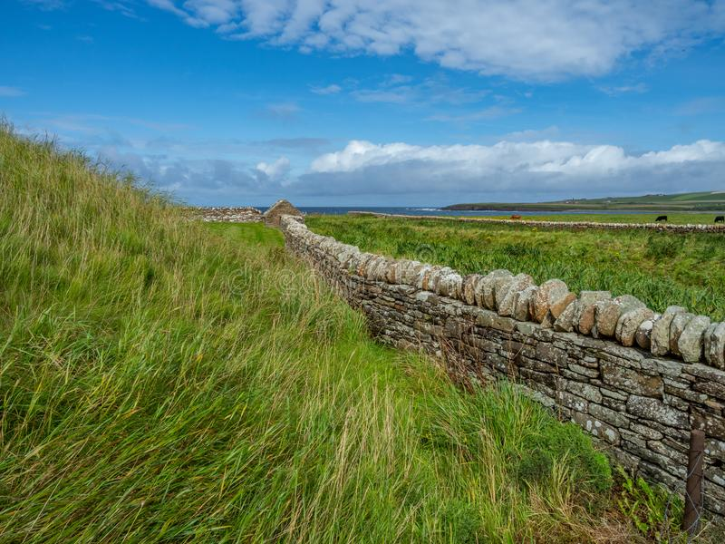 Skara Brae, Scottish Pompeii. Orkney, Scotland. Modern dry stone wall at Skara Brae, stone-built Neolithic settlement on the Bay of Skaill. UNESCO World Heritage royalty free stock image