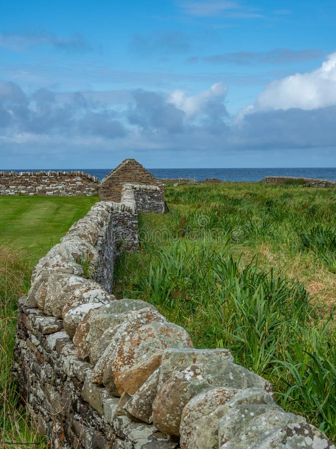 Skara Brae, Scottish Pompeii. Orkney, Scotland. Modern dry stone wall at Skara Brae, stone-built Neolithic settlement on the Bay of Skaill. UNESCO World Heritage royalty free stock images