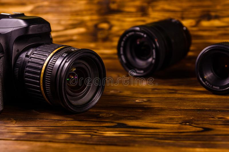 Modern dslr camera and lenses on wooden table. Modern dslr camera and lenses on rustic wooden table stock photos