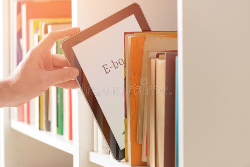 Modern ebook reader and books. Man taking modern ebook reader from a bookshelf royalty free stock images