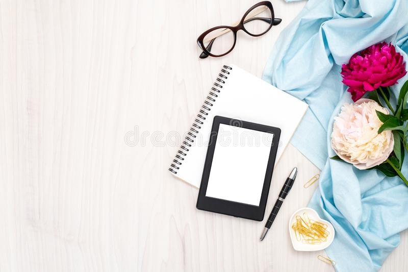 Modern ebook reader, paper notepad, peonies flowers, glasses, golden stationery on wooden background. Top view, minimal flat lay stock images