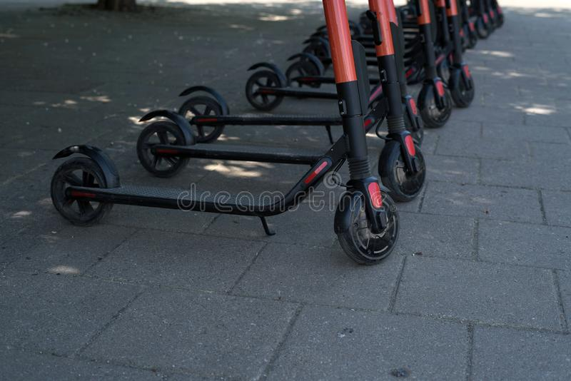 Modern eco electric city scooters for rent outdoors on the sidewalk. Alternative tourism, transportation around the city, bike stock photo