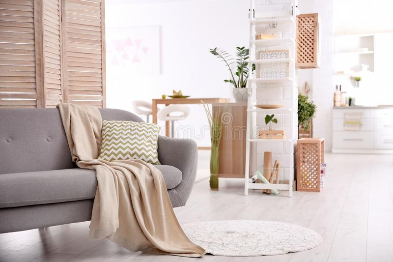 Modern eco style living room interior with wooden crates. Shelves and sofa stock photo