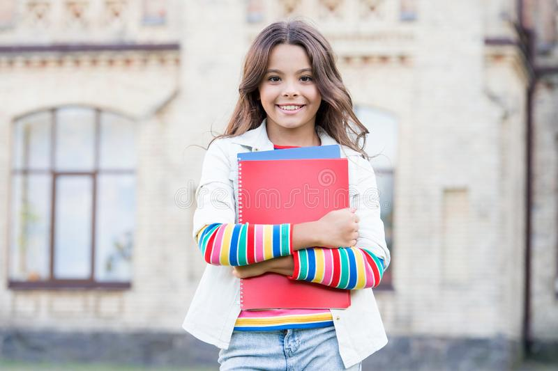 Modern education. Kid smiling girl school student hold workbooks textbooks for studying. Education for gifted children royalty free stock photo