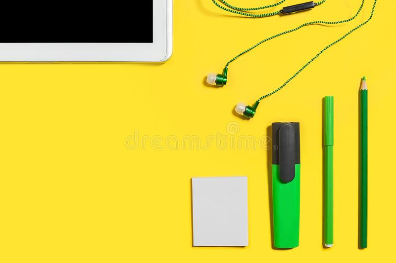 Modern educational accessories. Set of modern business or educational gadgets and accessories from the top view. green pencils, headphones, paper stickers royalty free stock photo
