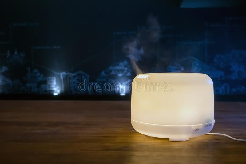 Modern electric aroma diffuser machine in operation stock photo