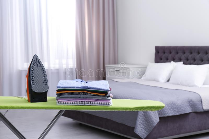 Modern electric iron and clean folded clothes on board in bedroom royalty free stock photo
