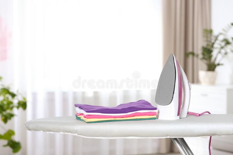 Modern electric iron and clean folded clothes on board in room. Space for text stock photo