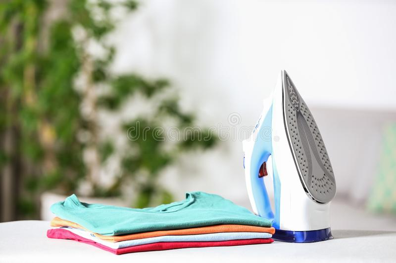 Modern electric iron and clean folded clothes on board in room. Space for text stock photos