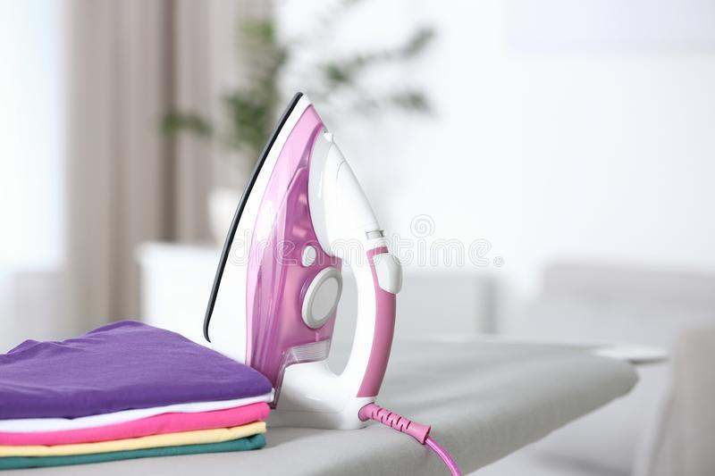 Modern electric iron and clean folded clothes on board in room. Space for text royalty free stock photography
