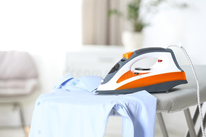 Modern electric iron and clean shirt on board indoors. Space for text stock photography