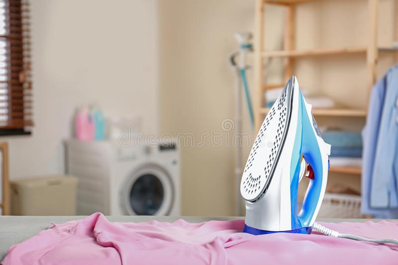 Modern electric iron and clean board in laundry room. Space for text. Modern electric iron and clean shirt on board in laundry room. Space for text stock image
