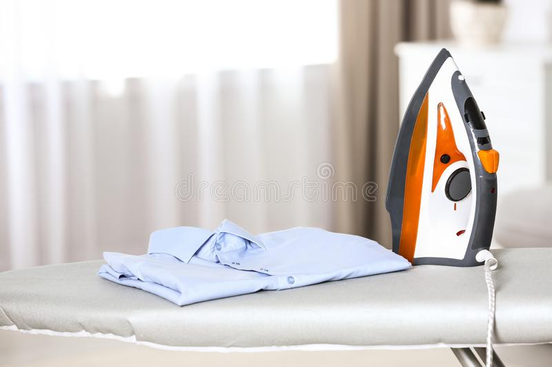 Modern electric iron and clean shirt on board in room. Space for text stock images