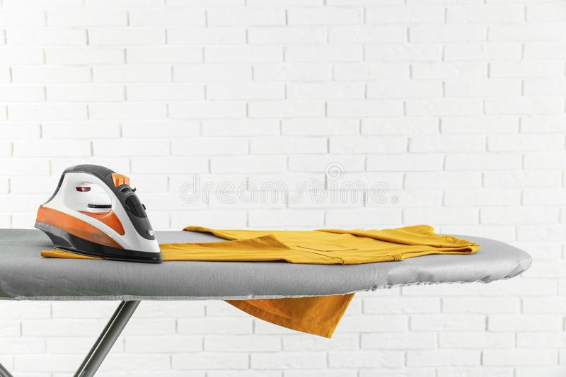 Modern electric iron and clean t-shirt on board against brick wall. Space for text stock photos