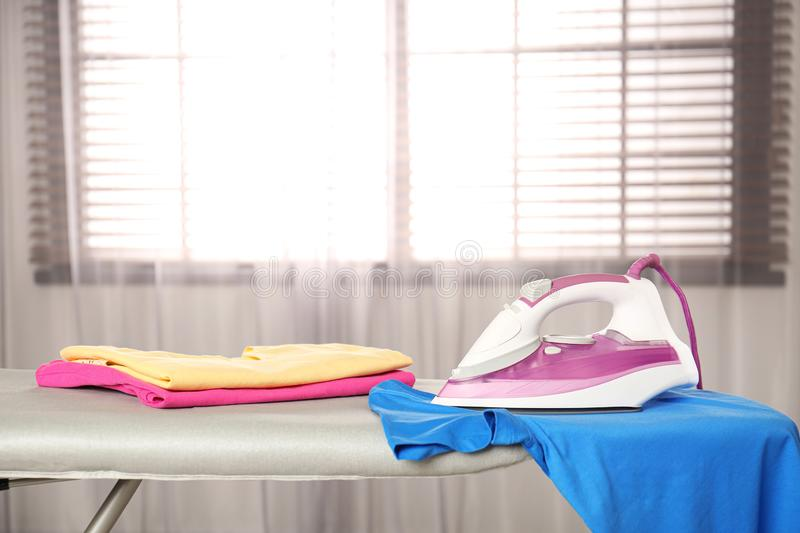 Modern electric iron and clean t-shirt on board indoors. Space for text stock images