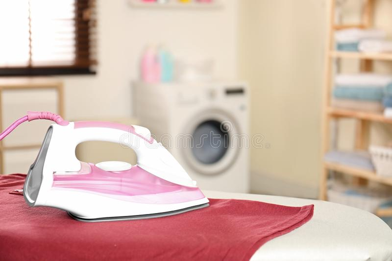 Modern electric iron and clean t-shirt on board in laundry room. Space for text royalty free stock image