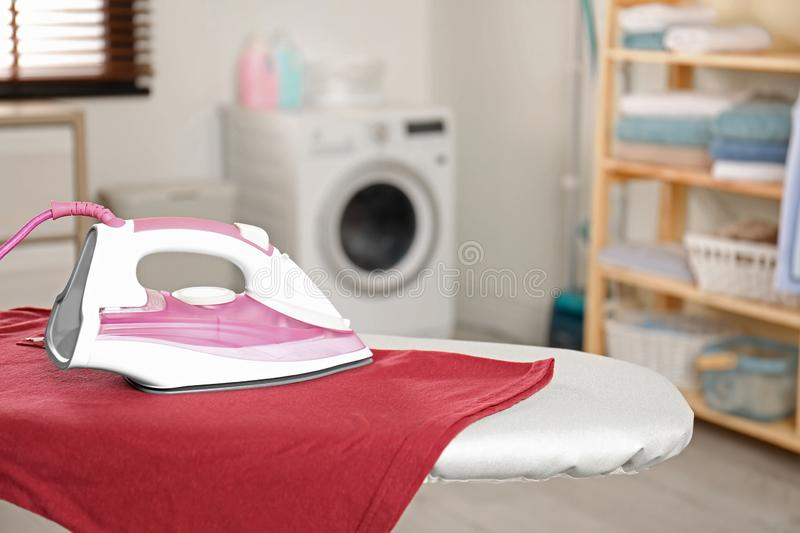 Modern electric iron and  t-shirt on board in laundry room. Space for text. Modern electric iron and clean t-shirt on board in laundry room. Space for text royalty free stock images