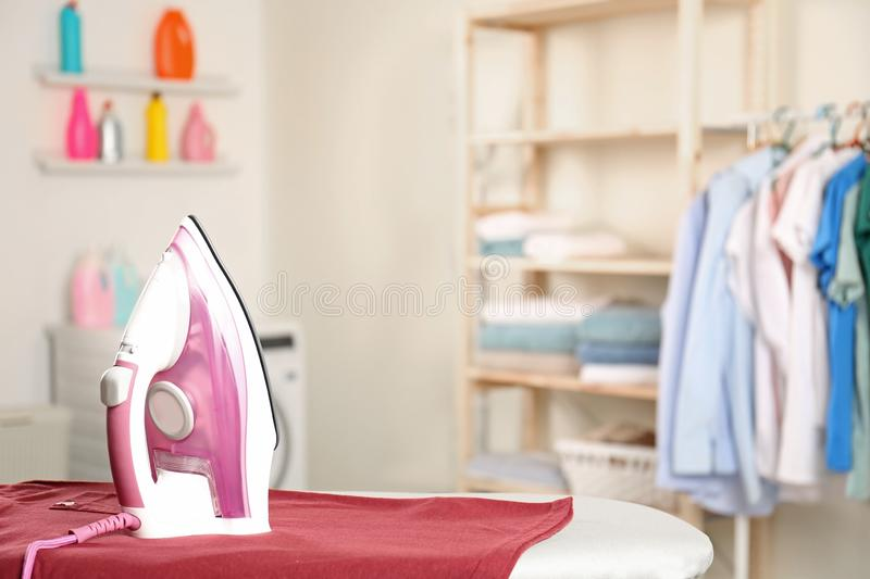 Modern electric iron and clean t-shirt on board in laundry room. Space for text stock photo