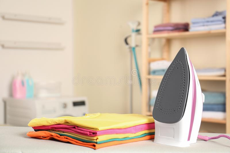 Modern electric iron and folded clothes on board in laundry room. Space for text stock image