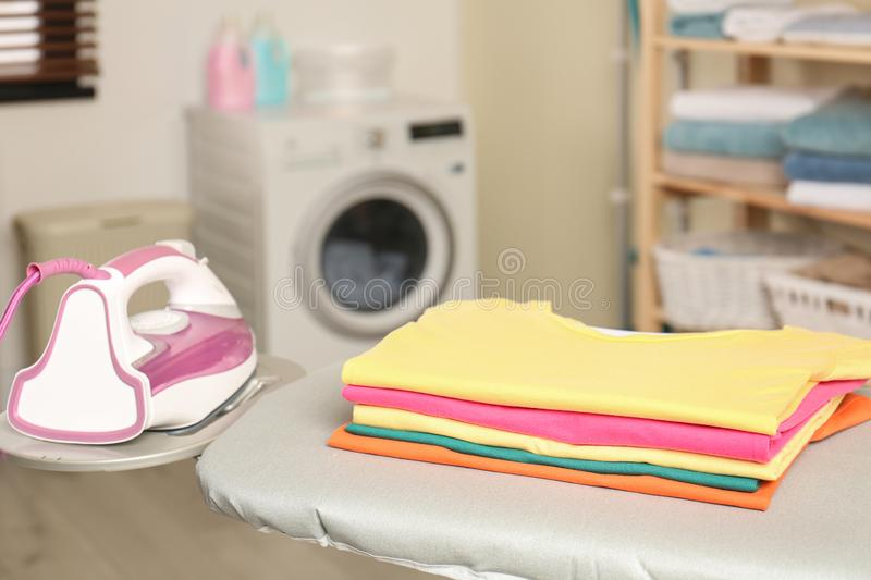 Modern electric iron and folded clothes on board in laundry room. Space for text royalty free stock images