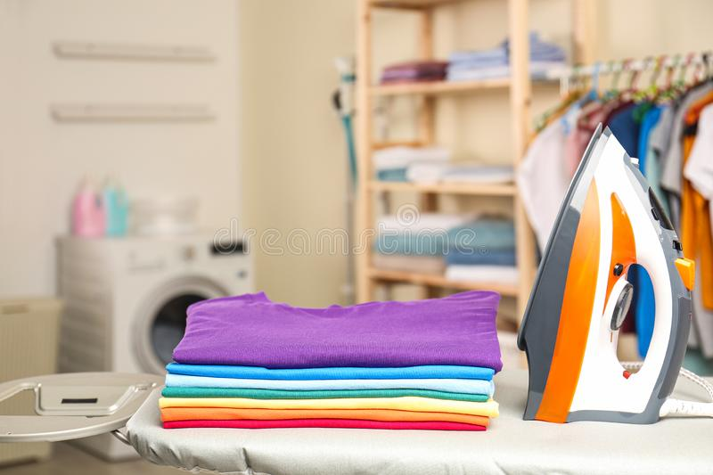 Modern electric iron and folded clothes on board in room. Space for text. Modern electric iron and folded clothes on board in laundry room. Space for text royalty free stock photography