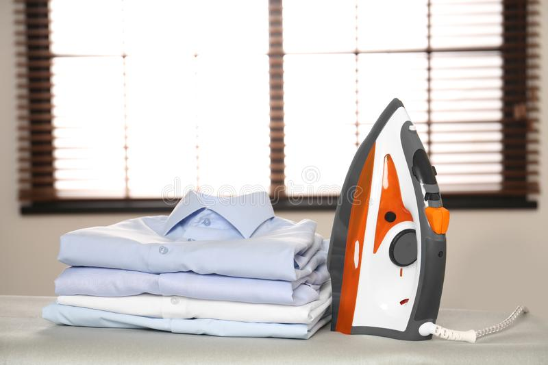 Modern electric iron and folded clothes on board. In room stock images
