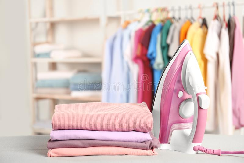 Modern electric iron and folded clothes on board. In room royalty free stock image