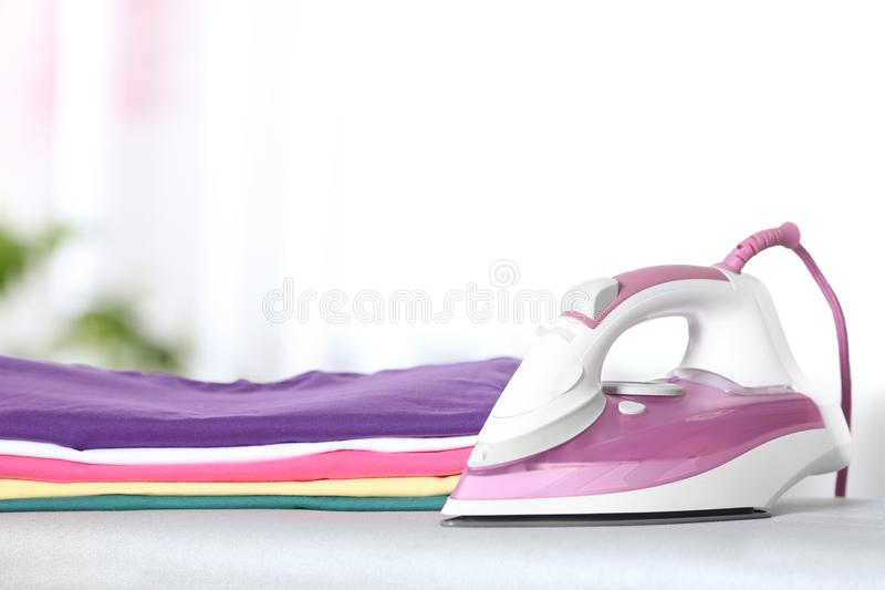 Modern electric iron and folded clothes on board in room. Space for text. Modern electric iron and clean folded clothes on board in room. Space for text stock photos