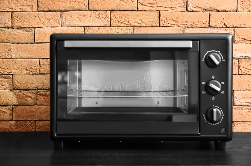 Modern electric oven on dark table stock photos