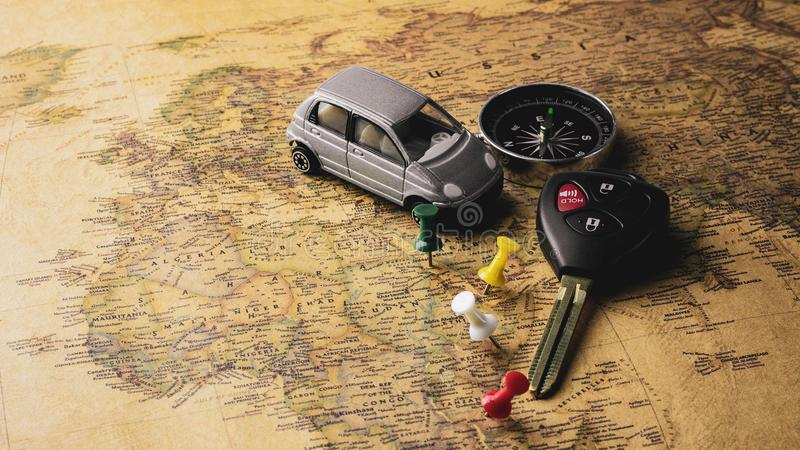 Modern electronic car keys and compass on vintage map. - travel and adventure concept. stock photo