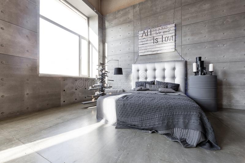 Modern empty bedroom in loft style with grey colors and wooden hand made Christmas tree with presents. royalty free stock photos