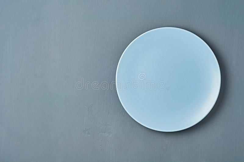Modern empty ceramic plate of blue color lies on dark concrete background. Space for text. Top view royalty free stock photo