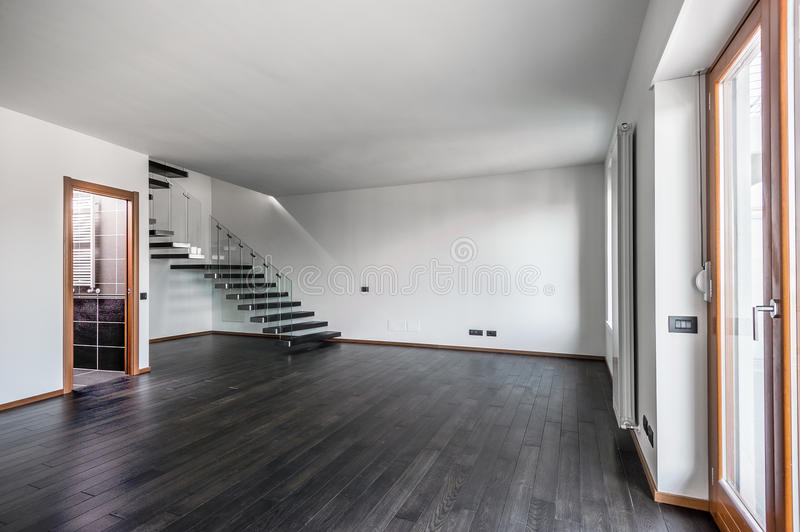 Modern empty interior with dark parquet and staircase royalty free stock photography