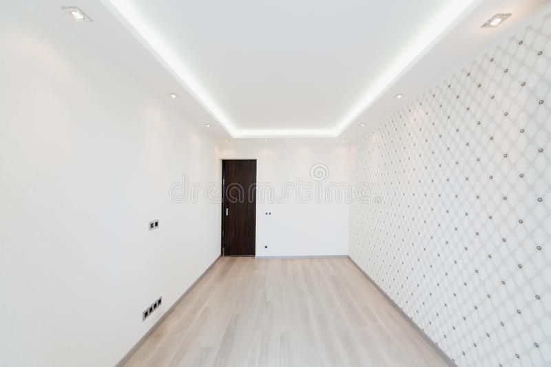 Modern empty room with a geometric pattern on the wall. And lighting around the perimeter of the ceiling stock photo