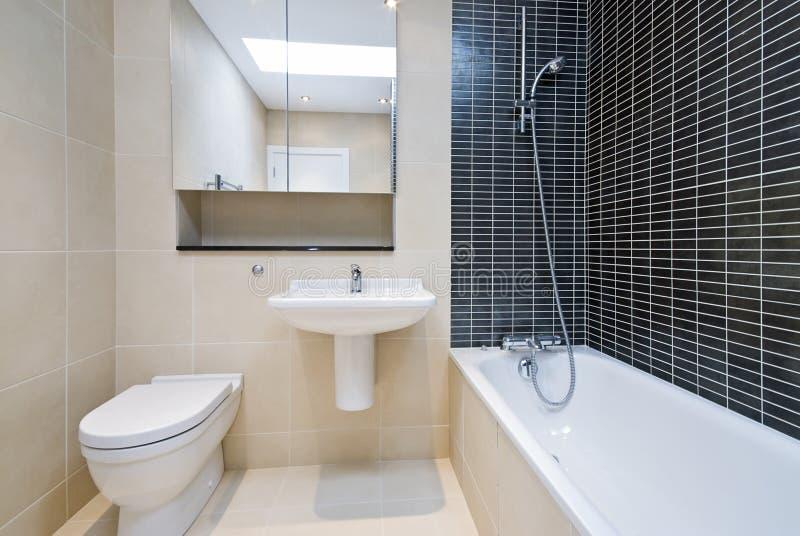 Modern en-suite bathroom in beige with black tiles stock photography