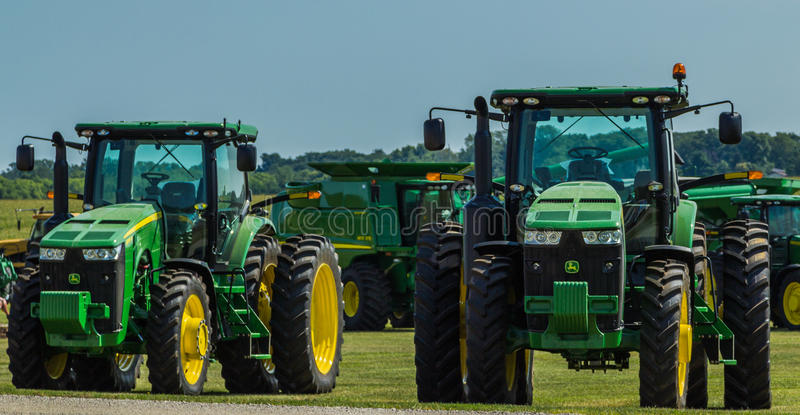 Modern Enclosed Cab John Deere Farm Tractors. These modern John Deere tractors have air conditioning and enclosed cabin's for the operator stock photography