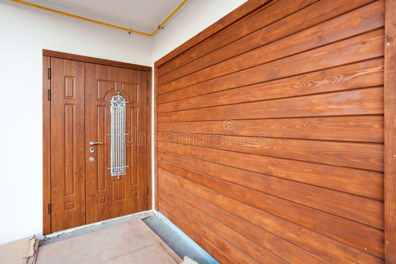 Modern entrance door with brown wooden panel. stock photos