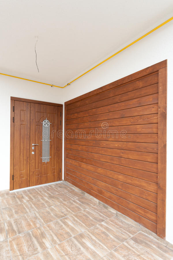 Modern entrance door with brown wooden panels. stock photo