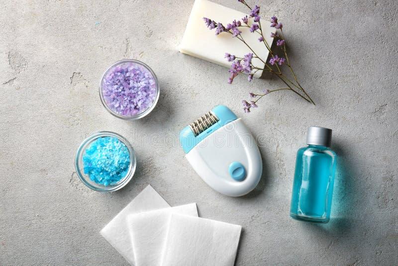 Modern epilator med kosmetiska produkter på grå bakgrund royaltyfria bilder