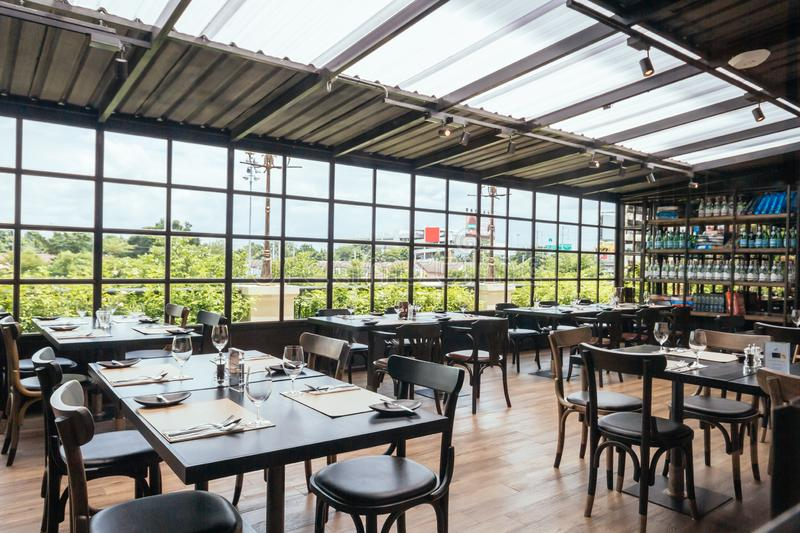 Modern European Restaurant in semi outdoor area with view from the outside and transparent roof stock photos