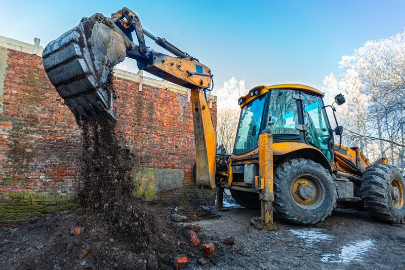 The modern excavator performs excavation work on the construction site. Front view of a digger bucket of digging ground. As a part of industry machinery royalty free stock images