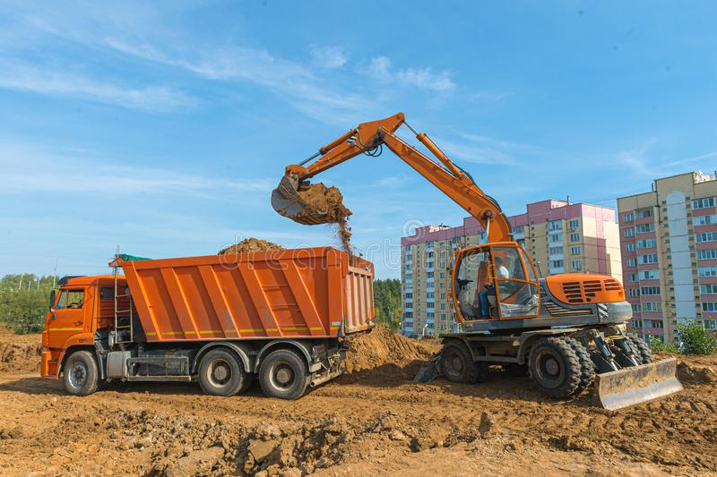 The modern excavator performs excavation work on the construction site. Excavator is loading excavation to the truck. Excavators hydraulic are heavy royalty free stock photography