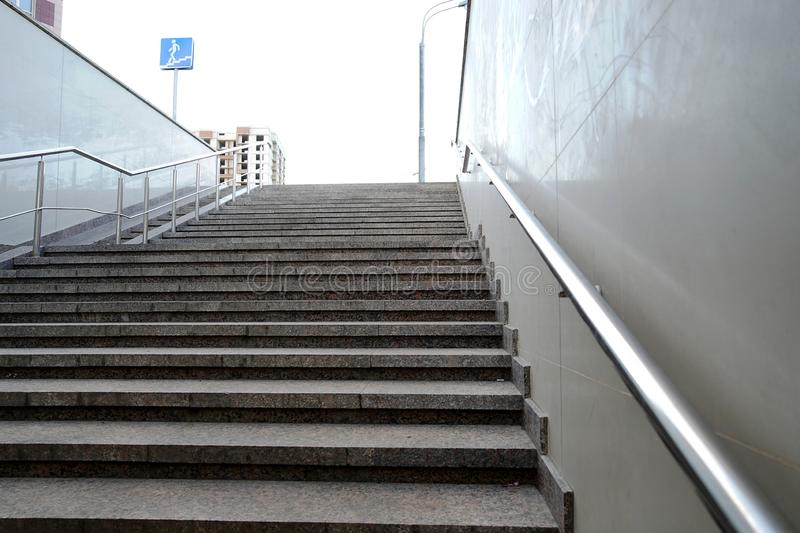 The modern exit from the pedestrian tunnel is empty, up the stairs. Staircase up to the street from the underpass. Stainless steel stock photography