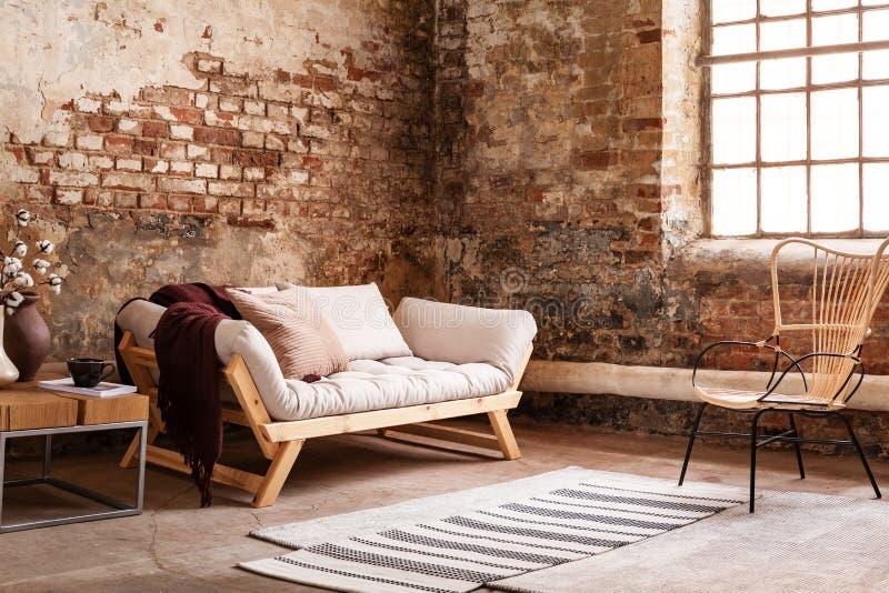 Modern fåtölj bredvid den gråa soffan i vindinre med fönstret royaltyfri foto